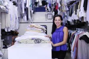 une propriétaire d'un nettoyeur pose fièrement dans son entreprise